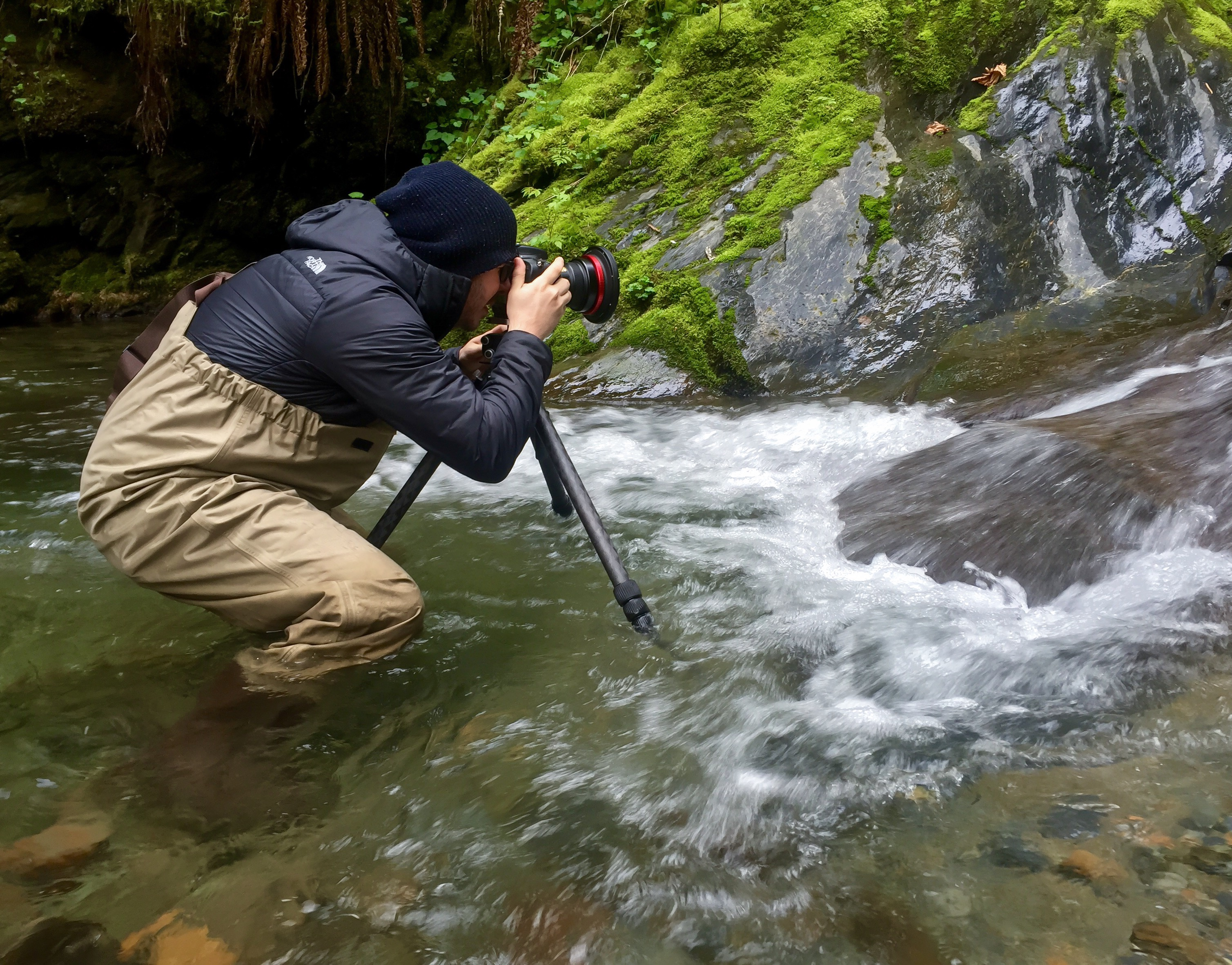Trying to stay warm in a snow-melt creek while photographing a waterfall.